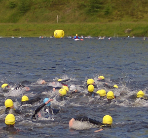 Triathlon competitors swimming in a lake