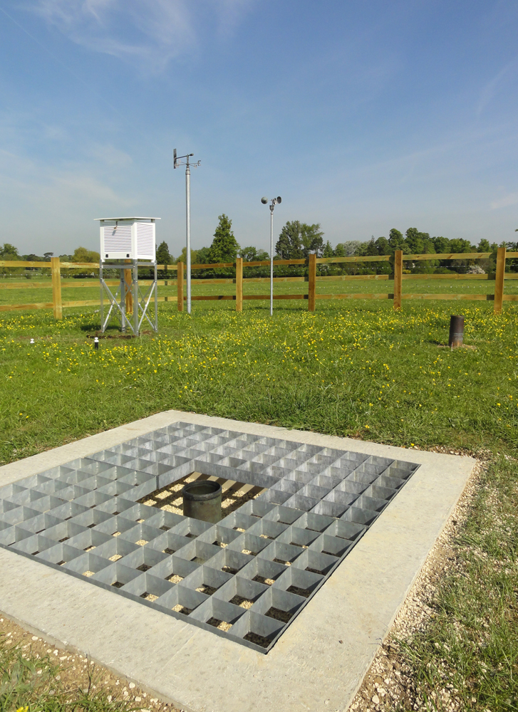 A ground level rain gauge in the foreground and a  Stevenson screen in the background at CEH's met station in Wallingford, Oxfordshire.  Photo: Harry Dixon/Centre for Ecology & Hydrology