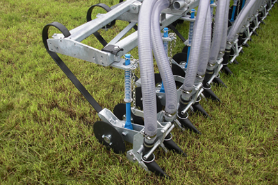 Discs cutting into soil to place slurry