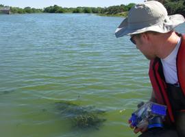 Scientist photographing algae on Loch Flemington