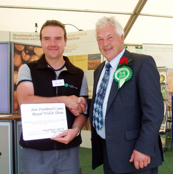CEH's Simon Grant accepts the award from Royal Welsh Show President, Trebor Edwards