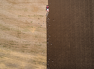 Aerial shot of a tractor ploughing a field
