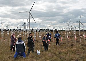 Scientists installing temperature and humidity sensors around wind turbines